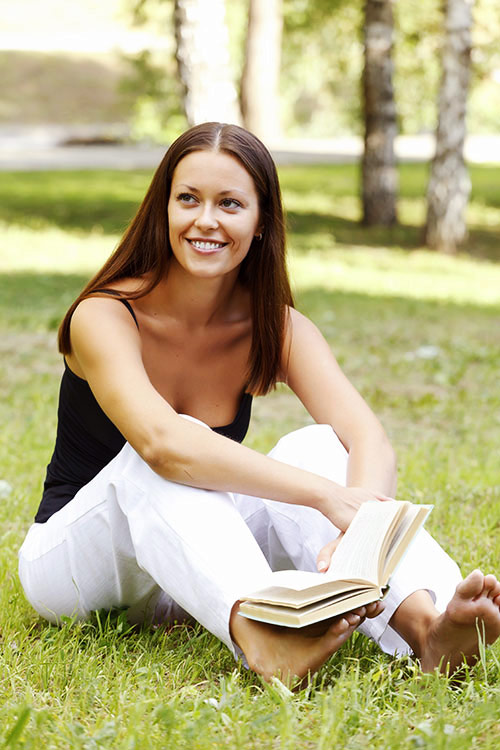woman sitting on grass with book